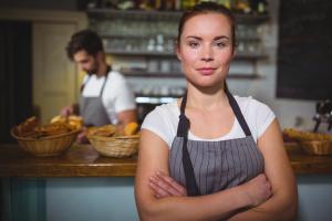 En kvinna i förgrunden i ett kafé