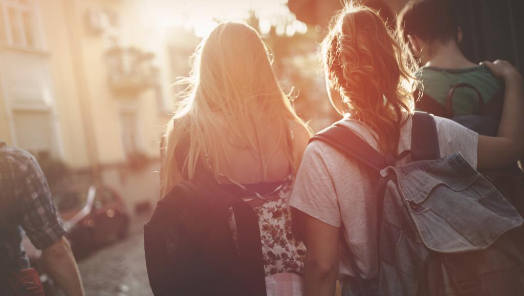 Tonåringar med ryggsäckar går över skolgården
