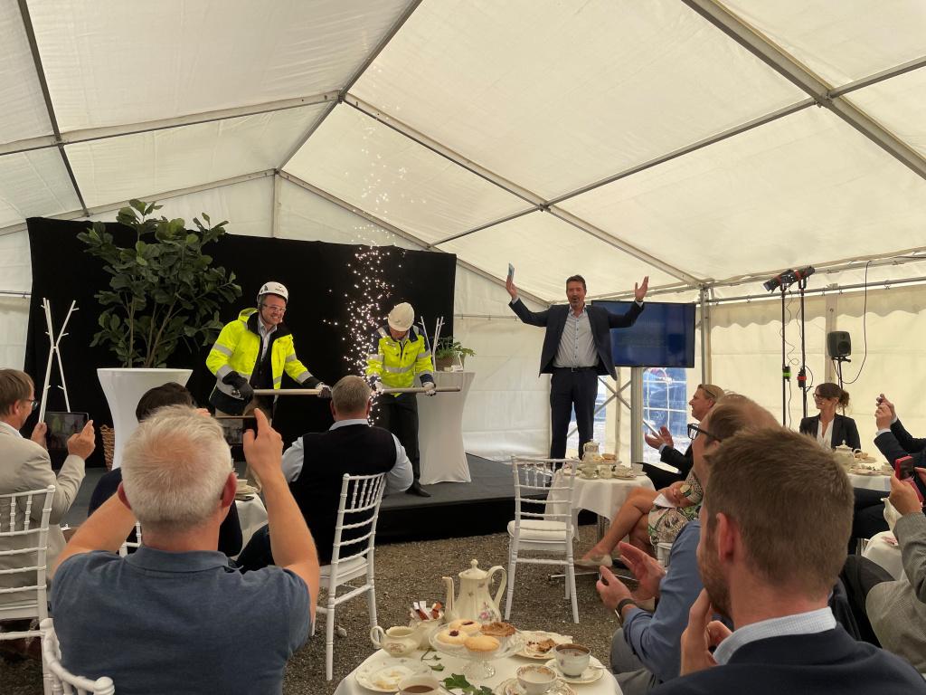 Olof Dahlgren fabrikschef för Nordic Sugar och Sezgin Kadir vd för Kraftringen kopplar samman första delen av den 1100 meter långa rörledning som ska leda fossilfritt producerad ånga mellan Nordic Sugars sockerbruk och Kraftringens kraftvärmeverk i Örtofta. Konferencier Johan Wester.